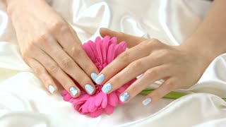 Pink gerbera and young manicured hands. Female hands with beautiful blue manicure touching gentle flower on white silk background. Womanhood and tidiness concept.