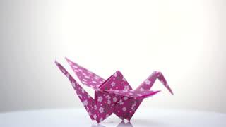 Pink patterned orizuru figurine on white. Traditional Japanese design of paper crane. Origami crafting workshop.