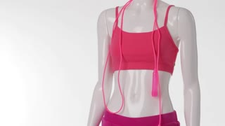 Pink sport shorts on mannequin. Lady's sports top and shorts. Mannequin with pink skipping rope. Female sports clothing on display.