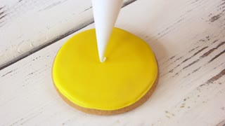 Piping a pattern on round yellow cookie. Decorating biscuit using piping bag. Guide for decoration of gingerbread cookies.