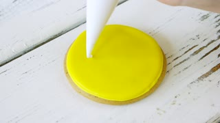 Piping smile on round yellow cookie. Smiley face cookie. Biscuit with yellow frosting. Dessert for good mood.