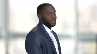 Playful black man in business suit. Bright blurred windows background.