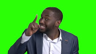 Playful dark-skinned businessman on green screen. Young cheerful afro-american man in formal wear inviting you to dance on chroma key background. Lets dance concept.