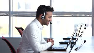 Pleasant call center worker, answering to questions. Man is saying goodbye on web camera, online converstation.