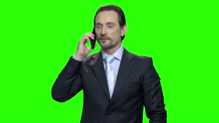 Portrait of a successful businessman talking on phone. Middle-aged man in suit. Green screen hromakey background for keying.