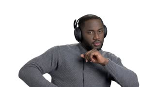 Portrait of a young black man listening to music in headphones. African man enjoying music in white isolated background.