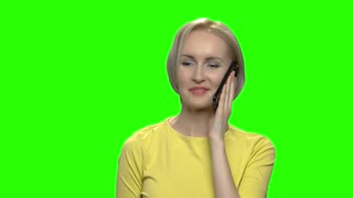 Portrait of beautiful blond mature woman talking on phone. Green hromakey background for keying.