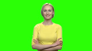 Portrait of beautiful blond woman with folded arms. Mature middle aged happy smiling female in yellow tshirt. Green hromakey background for keying.