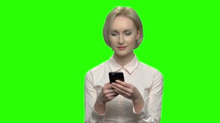 Portrait of beautiful blonde woman using her phone. Green screen hromakey background for keying.