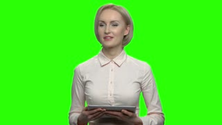 Portrait of beautiful woman using tablet device. Green screen hromakey background for keying.