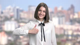 Portrait of cheerful female office worker. Cute young lady gesturing thumbs up with two hands, window city background. Human emotions and gestures.