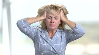Portrait of desperate woman on blurred background. Depressed mature woman pulling her hair. Stress and problems concept.