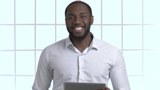 Portrait of handsome african black man holding tablet and talking. Black skin male manager explains and introducing indoor, checkered windows background.