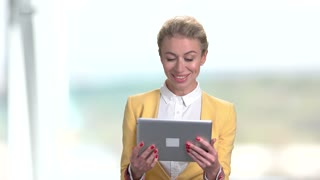 Portrait of happy business woman using tablet pc. Business lady watching funny videos or talking with someone using tablet. Bright blurred background.