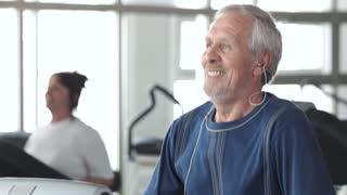 Portrait of happy male senior running on treadmill. Smiling elderly man doing cardio exercise at gym. Fitness for seniors.