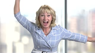 Portrait of happy middle-aged business woman in office rejoicing success. Emotional screaming entrepreneur rejoicing in victory. Bright blurred background.