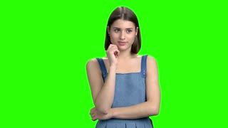 Portrait of happy pretty woman cheered up. Cheerful girl in denim blue dress. Green screen hromakey background for keying.