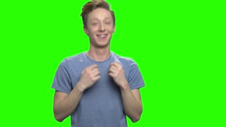 Portrait of happy teenage boy dancing. Green screen hromakey background for keying.