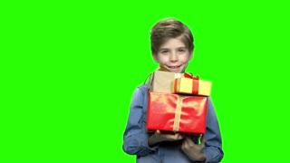 Portrait of little boy in denim jacket with gift boxes. Green hromakey background for keying.