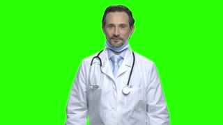 Portrait of male doctor puts on medical protective mask. Green screen hromakey background for keying.