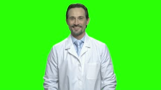 Portrait of mature smiling doctor with thumb up. White medical coat. Green hromakey background for keying.