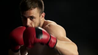 Portrait of muscular kickboxer, black background. Young caucasian boxer fighting on ring, slow motion. Confident boxing champion.