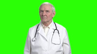Portrait of old frown doctor sighing. Doctor is preparing to tell bad news and breathing hard. Hromakey background.