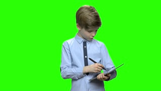 Portrait of smart boy drawing on tablet pc. Green hromakey background for keying.