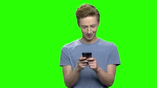 Portrait of teenager holding smartphone and chatting. Emotional facial expressions. Green screen hromakey background for keying.