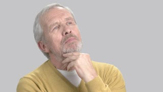 Portrait of thinking man, grey background. Caucasian elderly man looking thoughtful. Recollection of sweet memories.