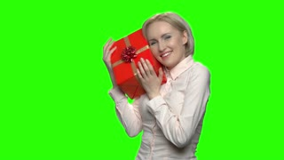Portrait of woman admires her gift box for birthday. Excited mature caucasian woman with red gift box and ribbon. Green hromakey background for keying.