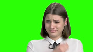 Portrait of young crying girl. Sad woman weeping with handkerchief. Green screen hromakey background for keying.
