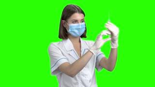 Portrait of young female doctor prepare syringe. Physician in white medical uniform. Green screen hromakey background for keying.