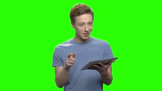 Portrait of young teenage boy talking holding tablet. Teen boy talking on green hromakey background.