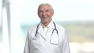 Portrait old doctor laughing hard. Senior physician with stethoscope in bright abstract background.
