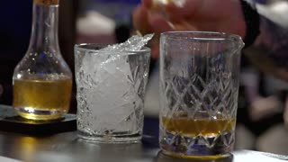 Pouring alcohol drink in the glass. Rum pouring. close up, slow motion.