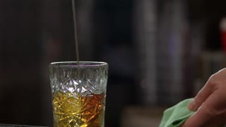 Pouring rum, slow motion. Glass of alcohol drink, close up.
