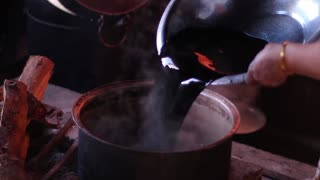 Preparation of dye for fabrics. Cooking on the furnace. Ancient culture.