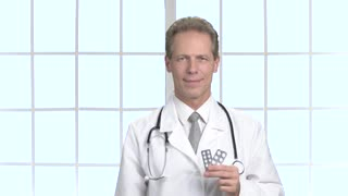 Professional doctor showing medication pills. Middle aged male doctor showing new effective medical pills. Medicine, healthcare and pharmacy concept.