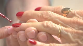 Professional manicure in nail salon close up. Nail beautician applying red lacquer to senior woman nails in beauty studio close up.