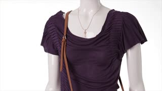 Purple t-shirt in the wind. Dark purple garment on mannequin. Dark t-shirt with key necklace. Casual t-shirt on white background.