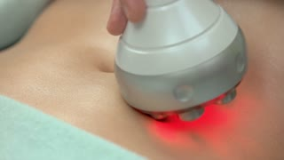 Radio frequency skin tightening machine. Female belly close up, cosmetology.