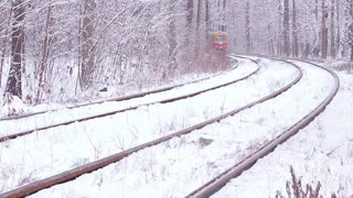 Railway in the forest. Public transport. Retro tram in winter. Train goes through the snowy wood.