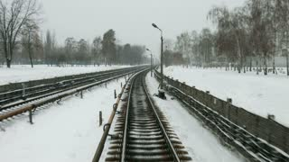 Railway in the winter. High-speed train goes in the winter season. Snow flies in the window of the driver. Long track.