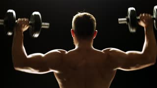 Rear view bodybuilder lifting a dumbbells. Young bodybuilder training with dumbbells on black background. Perfect muscles of back.