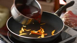 Red liquid pours on pan. Hand is touching frying pan. Orange peel and dark liquid. Wine mixed with orange skin.