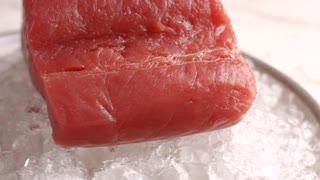 Red meat lying on ice. Plate with raw fish meat. Food ingredient of high quality. Product stored at low temperature.