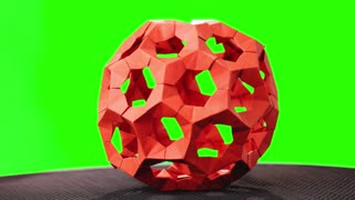 Red modular origami ball on green screen. Beautiful object of paper art on chroma key background. Japanese paper handicraft.