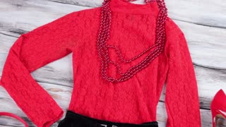 Red top with black skirt. Bead necklace and evening top. New design and quality fabric. Girl's clothing on wooden showcase.