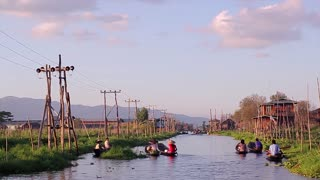 Residents of Lake Inle floating from work to home. People floating in boats on the beautiful lake.